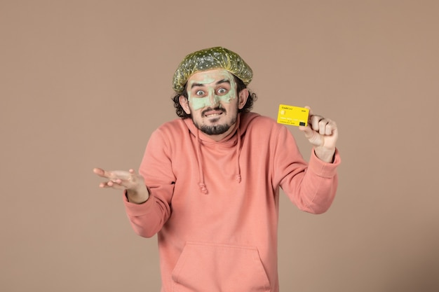 Vue de face jeune homme tenant une carte de crédit jaune sur fond marron thérapie de salon de peau soins de la peau soins du visage argent