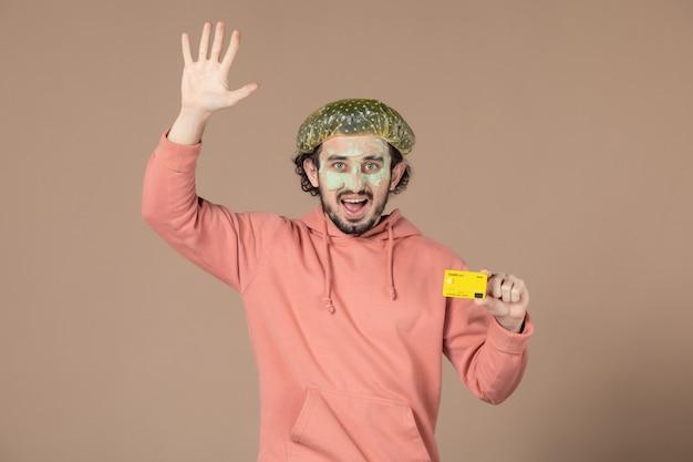 Vue de face jeune homme tenant une carte de crédit jaune sur fond marron thérapie de salon de la peau soins de la peau soins du visage spa argent