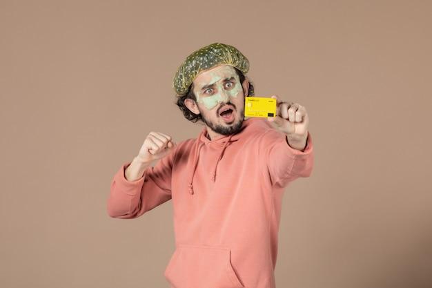 Vue de face jeune homme tenant une carte de crédit jaune sur fond marron thérapie de salon de la peau soins de la peau soins du visage spa couleur argent