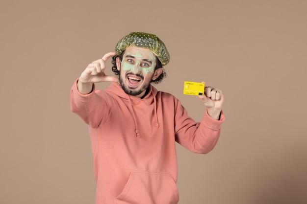 Vue de face jeune homme tenant une carte de crédit jaune sur fond marron thérapie salon de la peau soins de la peau soins du visage spa