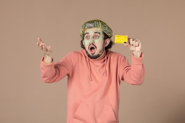 Vue de face jeune homme tenant une carte de crédit jaune sur fond marron thérapie de salon de la peau soins de la peau spa du visage argent