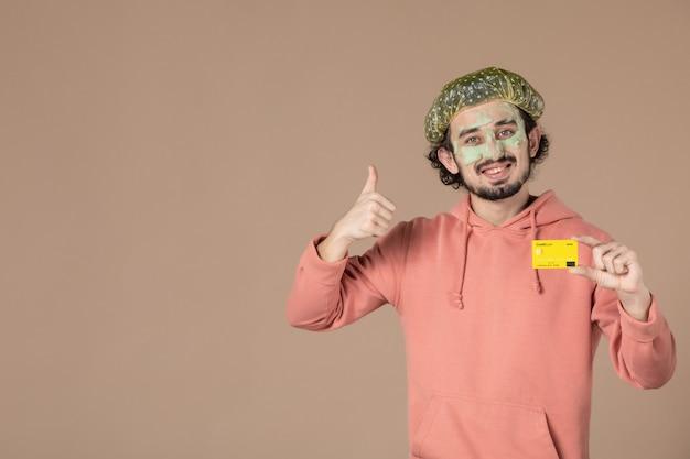 Vue de face jeune homme tenant une carte de crédit jaune sur fond marron thérapie de soins du corps spa salon de soins peau du visage