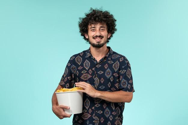 Vue de face jeune homme tenant des cips de pommes de terre sur le mur bleu cinéma masculin cinéma cinéma