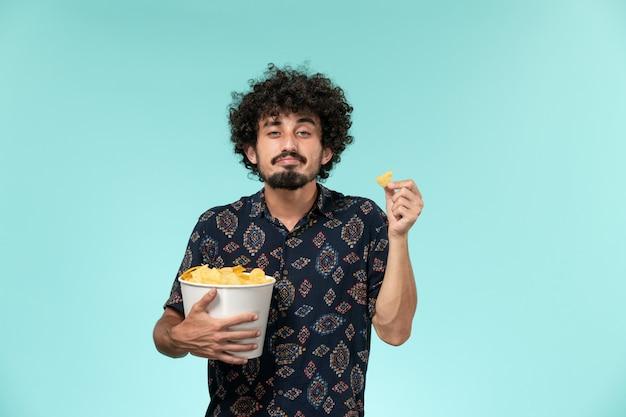 Vue de face jeune homme tenant des cips de pommes de terre sur mur bleu clair cinéma films cinéma mâle