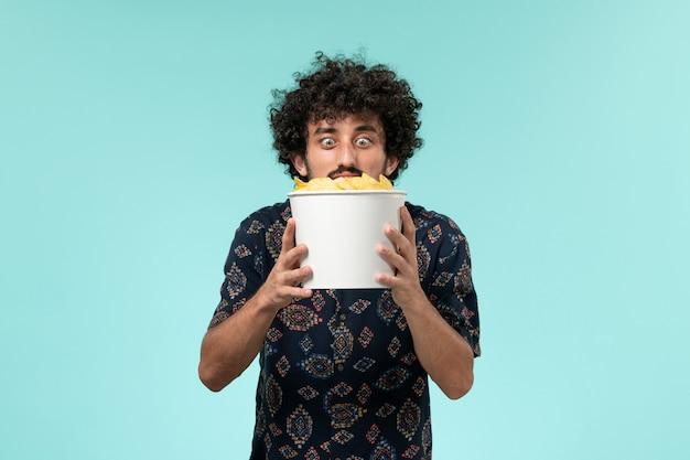 Vue de face jeune homme tenant des cips de pommes de terre sur le mur bleu clair mâle cinéma cinéma cinéma