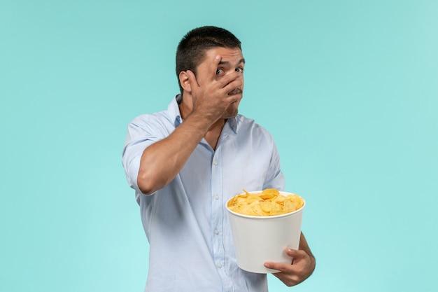 Vue de face jeune homme tenant des cips de pommes de terre et regarder un film sur le mur bleu cinéma films à distance solitaire