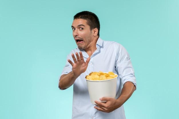 Vue de face jeune homme tenant des cips de pommes de terre et regarder un film sur un mur bleu clair cinéma films à distance solitaire