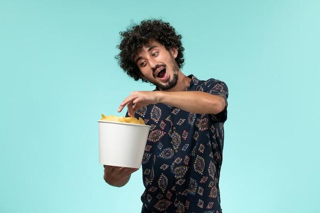 Vue de face jeune homme tenant des cips de pommes de terre et regarder un film sur un mur bleu mâle cinéma films cinéma cinéma