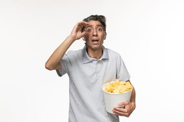 Vue de face jeune homme tenant des croustilles sur une surface blanche