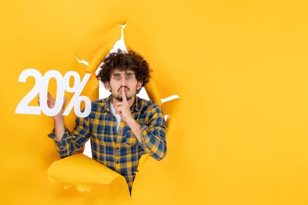 Vue de face jeune homme tenant écrit sur fond jaune clair