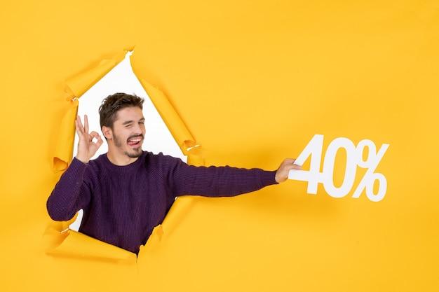 Vue de face jeune homme tenant écrit sur fond jaune couleur shopping photo cadeau de vacances noël