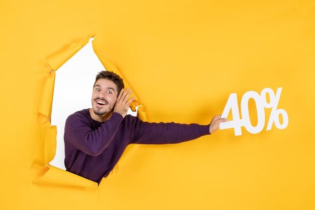 Vue de face jeune homme tenant écrit sur fond jaune couleur shopping photo cadeau vacances de noël