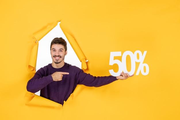Vue de face jeune homme tenant écrit sur fond jaune shopping cadeau de noël couleur photo de vacances