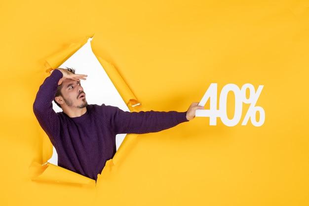 Vue de face jeune homme tenant écrit sur fond jaune shopping cadeau de noël photo couleurs vacances