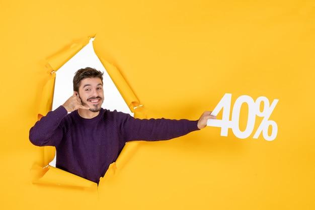 Vue de face jeune homme tenant écrit sur fond jaune shopping cadeau de vacances couleurs photo de noël