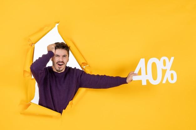 Vue de face jeune homme tenant écrit sur fond jaune shopping couleur photo cadeau de noël