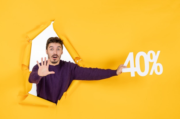 Vue de face jeune homme tenant écrit sur fond jaune shopping couleur photo cadeau de vacances de noël