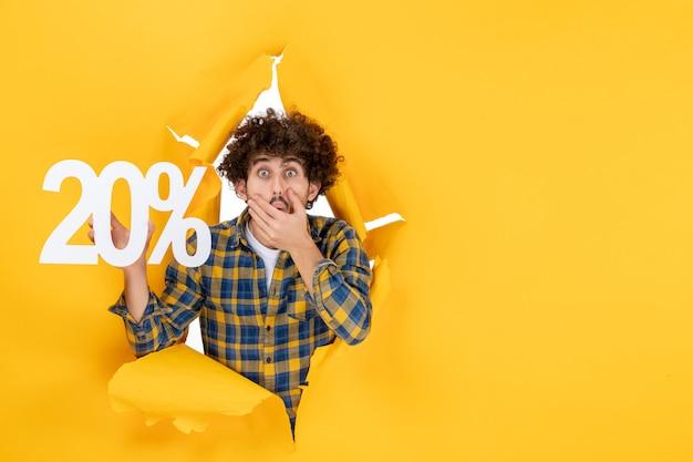Vue de face jeune homme tenant écrit sur fond jaune