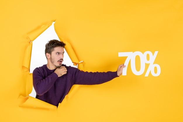 Vue de face jeune homme tenant l'écriture sur fond jaune couleur shopping cadeau de vacances argent photo de noël