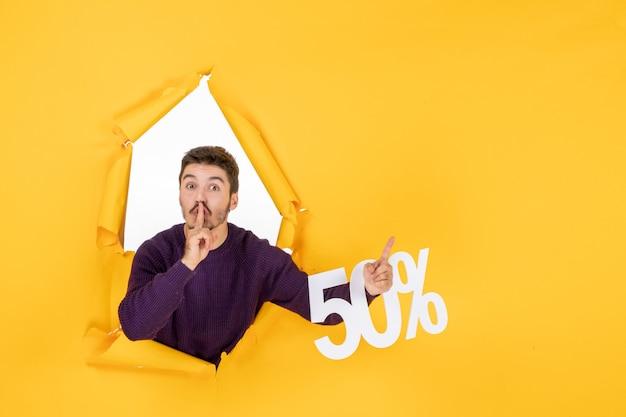 Vue de face jeune homme tenant l'écriture sur fond jaune photo cadeau vente couleurs noël shopping vacances