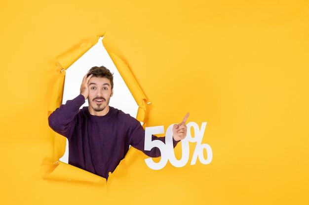 Vue de face jeune homme tenant l'écriture sur fond jaune photo couleur cadeau vente noël shopping vacances