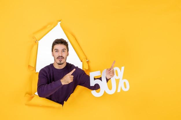 Vue de face jeune homme tenant l'écriture sur fond jaune photos vacances cadeau vente couleur noël shopping