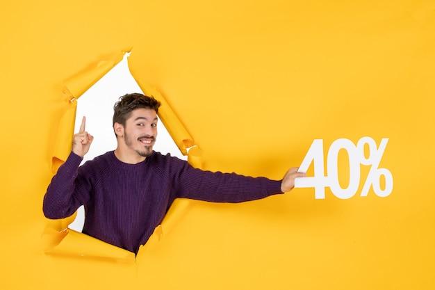 Vue de face jeune homme tenant l'écriture sur fond jaune shopping noël vacances cadeau photo couleurs