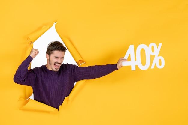 Vue de face jeune homme tenant l'écriture sur fond jaune shopping noël vacances cadeau photos couleur