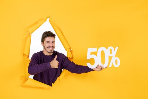 Vue de face jeune homme tenant l'écriture sur fond jaune shopping vacances de noël couleur cadeaux vente photo magasin du nouvel an