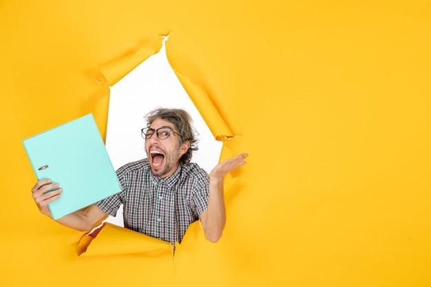 Vue de face jeune homme tenant un fichier vert sur fond jaune couleur bureau émotion travail de vacances travail de noël