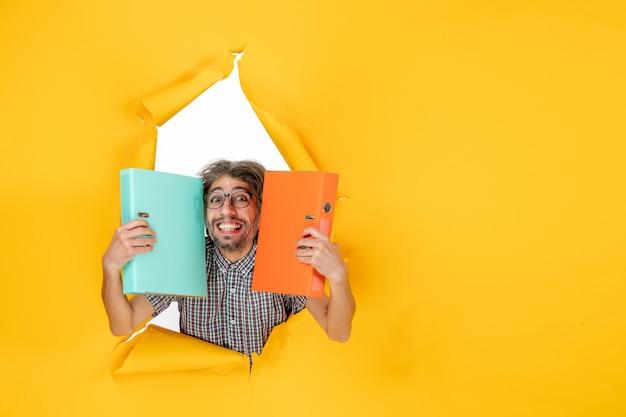 Vue de face jeune homme tenant un fichier vert sur fond jaune couleur bureau émotion vacances travail de noël