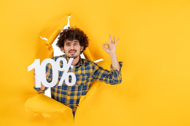 Vue de face jeune homme tenant sur fond jaune