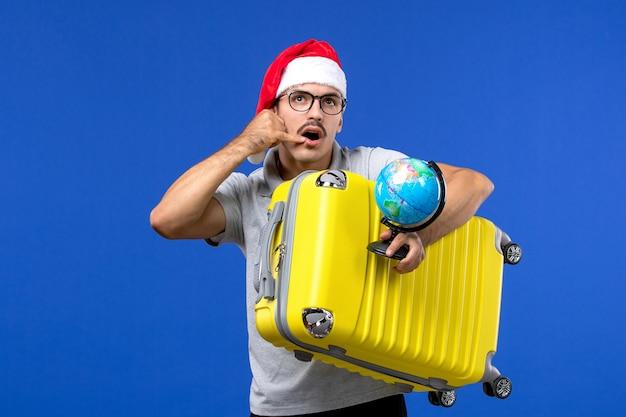 Vue de face jeune homme tenant globe et sac jaune sur avion de voyage de vacances mur bleu