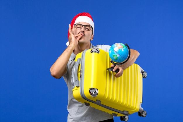 Vue de face jeune homme tenant globe et sac jaune sur le voyage de vacances avions mur bleu