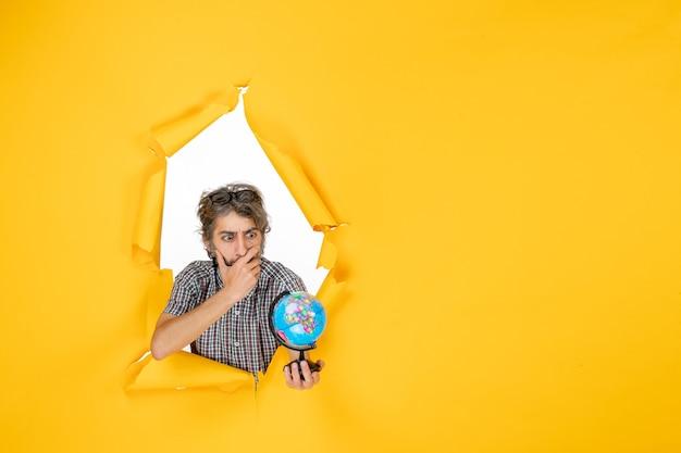 Vue de face jeune homme tenant un globe terrestre sur fond jaune planète noël vacances monde pays émotion couleur