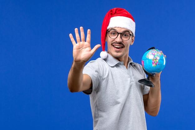 Vue de face jeune homme tenant le globe terrestre sur le mur bleu avion vacances mâle