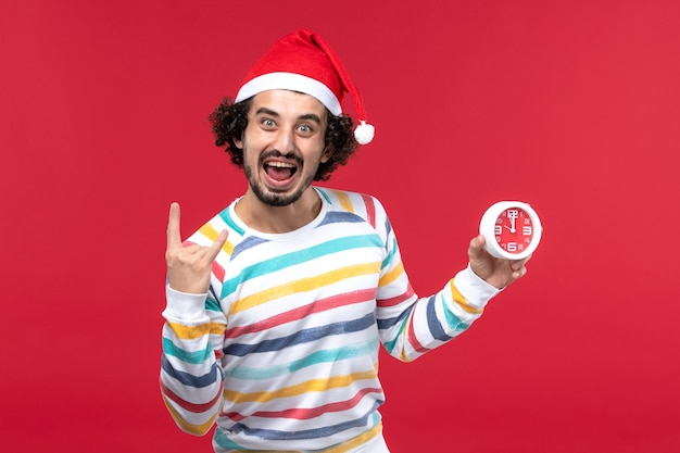 Vue de face jeune homme tenant heureusement des horloges sur le mur rouge temps vacances nouvel an mâle rouge