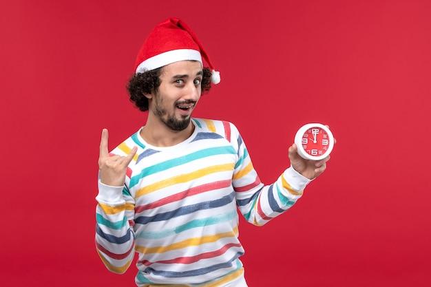 Vue de face jeune homme tenant heureusement des horloges sur le mur rouge vacances nouvel an mâle rouge