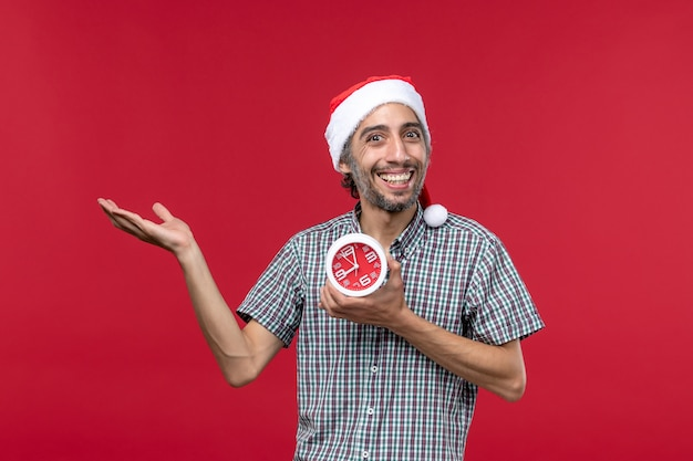 Vue de face jeune homme tenant des horloges avec une expression souriante sur le mur rouge temps d'émotion rouge