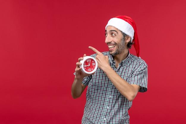 Vue de face jeune homme tenant des horloges rondes sur le fond rouge