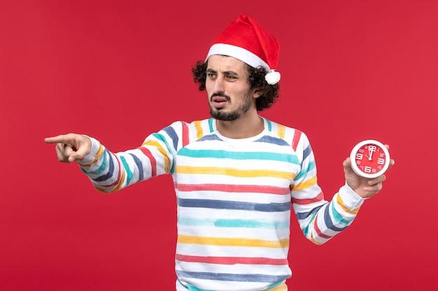 Vue de face jeune homme tenant des horloges rondes sur le mur rouge temps nouvel an vacances mâle rouge