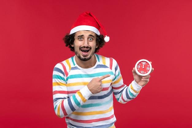 Vue de face jeune homme tenant des horloges rondes sur le mur rouge temps nouvel an vacances rouge