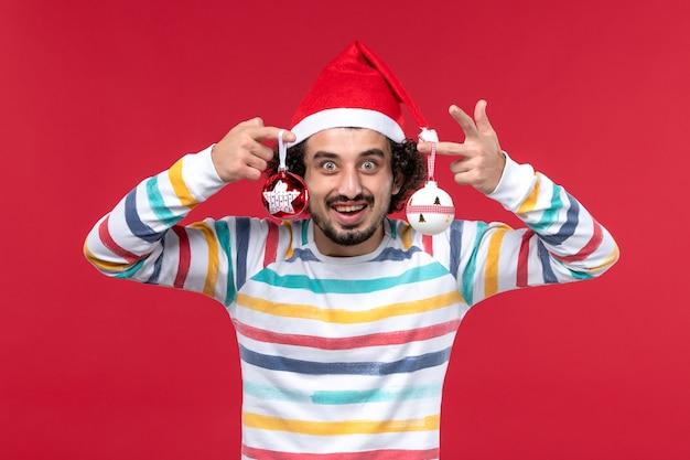 Vue de face jeune homme tenant le jouet d'arbre de noël sur le mur rouge nouvel an vacances rouge