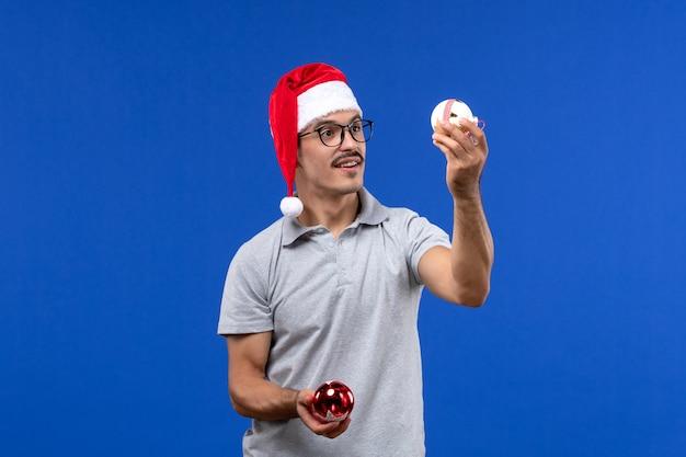 Vue de face jeune homme tenant des jouets d'arbre en plastique sur fond bleu homme vacances nouvel an