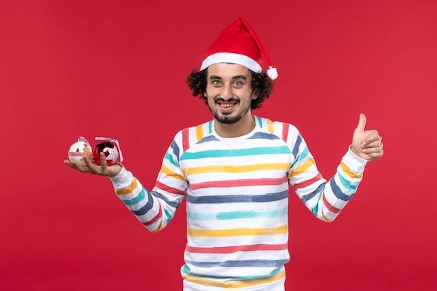 Vue de face jeune homme tenant des jouets en plastique sur le mur rouge rouge les humains vacances du nouvel an