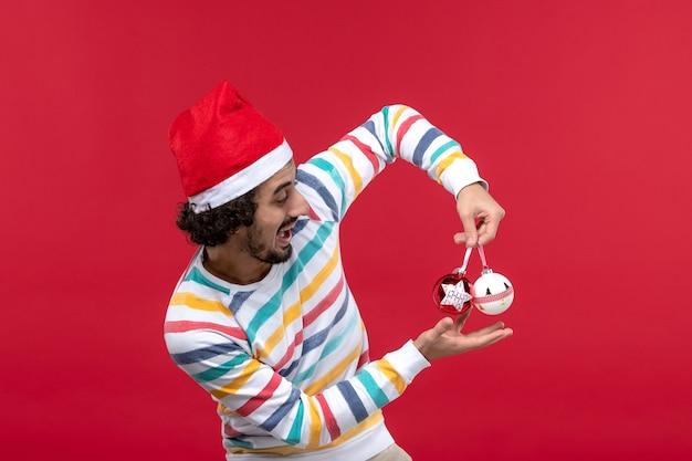 Vue de face jeune homme tenant des jouets en plastique sur le mur rouge vacances humaines nouvel an rouge