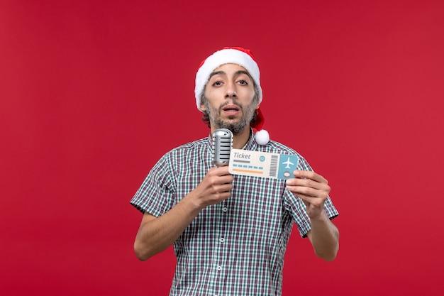 Vue de face jeune homme tenant micro et billet d'avion sur fond rouge