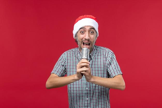 Vue de face jeune homme tenant un micro sur un bureau rouge