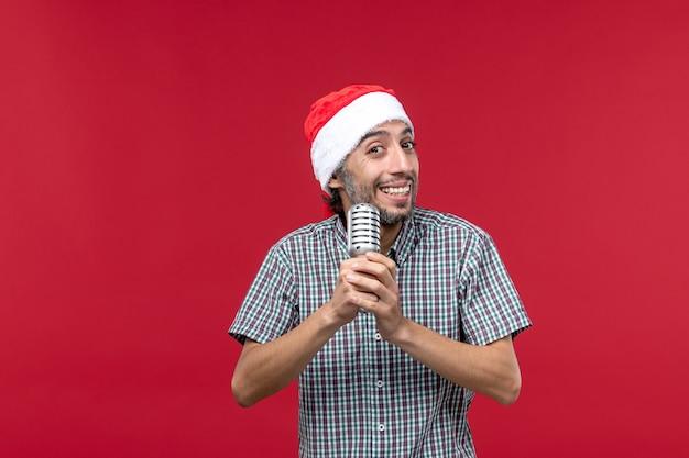 Vue de face jeune homme tenant micro et chantant sur un bureau rouge
