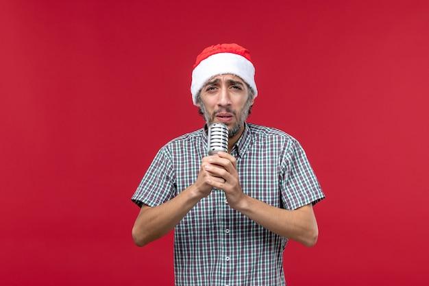 Vue de face jeune homme tenant micro et chantant sur fond rouge